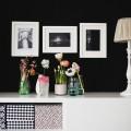 Eine Wohnzimmerecke mit schwarzer Wand und frischen Frühlingsblumen